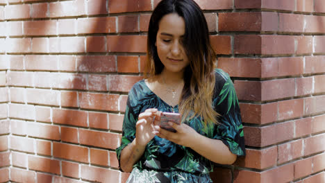 Woman-leaning-on-a-brick-wall-using-a-mobile