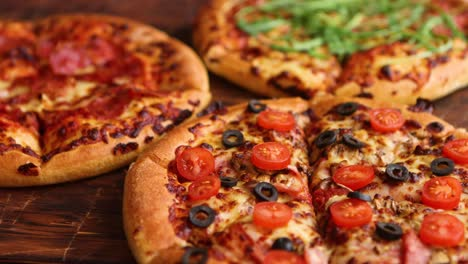 Various-kinds-of-pizzas-placed-on-wooden-table