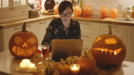 Woman-with-laptop-amidst-Halloween-decorations