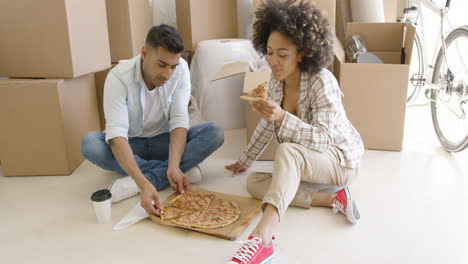 Young-couple-tucking-into-a-pizza