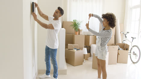 Young-couple-hanging-pictures-in-their-new-home