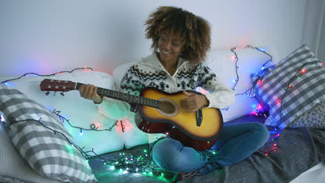 Cheerful-woman-playing-guitar-in-garland-lights