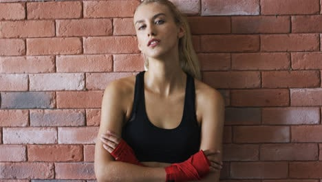 Positive-sportswoman-leaning-on-brick-wall