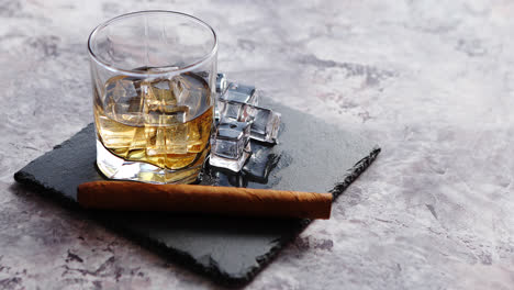 Glass-of-whiskey-with-ice-cubes-and-cigar