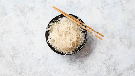 Close-up-of-bowl-of-noodles-with-wooden-chopsticks