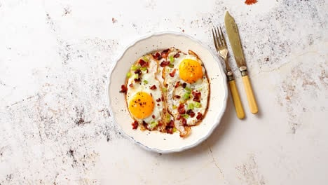 Two-fresh-fried-eggs-with-crunchy-crisp-bacon-and-chive-served-on-rustic-plate