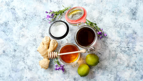 Healthy-food-table-with-different-kinds-of-honey-fresh-ginger-and-lime