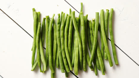 Fresh-green-bean-pods-placed-on-white-wooden-table