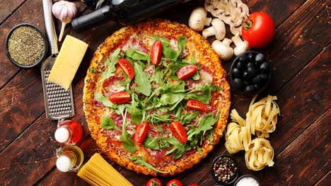 Italian-food-background-with-pizza--raw-pasta-and-vegetables-on-wooden-table