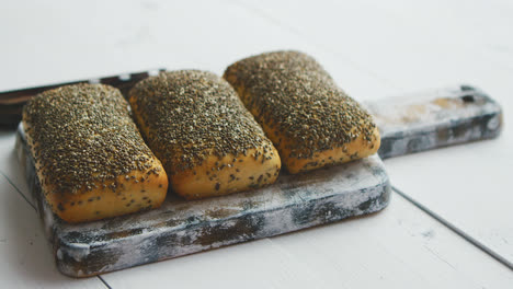 Closeup-of-whole-grain-bread-with-seeds-on-a-rustic-wooden-board