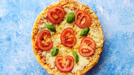 Pizza-with-cheese-and-tomatoes-on-blue-stone-table