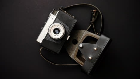 Old-retro-film-camera-in-leather-case-on-black-background