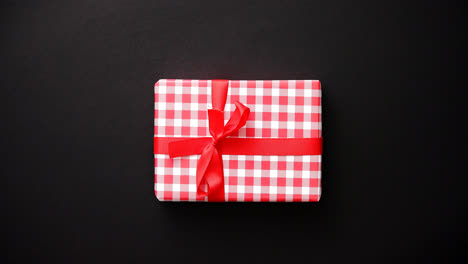 Red-gift-box-with-red-bow-on-black-table-top-view