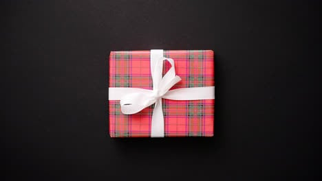 Red-gift-box-with-white-bow-on-black-table-top-view
