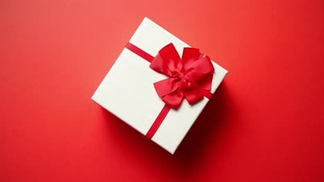 Top-view-on-gift-wrapped-in-striped-gift-paper-decorated-with-ribbon-on-red