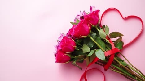 Mixed-flowers-bouquet-with-roses-and-heart-shaped-bow-on-pink-background