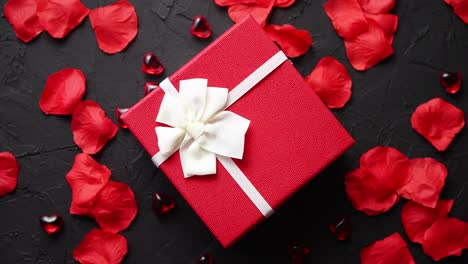 Gift-box-on-black-stone-table-Romantic-holiday-background-with-rose-petals