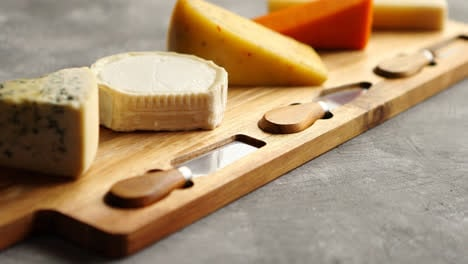 Assortment-of-various-kinds-of-cheeses-served-on-wooden-board-with-fork-and-knives
