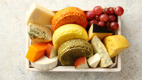 Fresh-and-delicious-different-kinds-of-cheeses-placed-in-wooden-crate-with-grapes