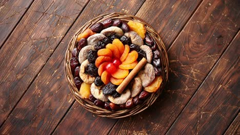Mix-of-dried-fruits-in-a-small-wicker-basket-on-wooden-table
