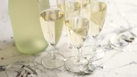 Champagne-glasses-and-bottle-placed-on-white-marble-background