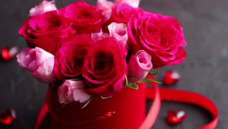 Pink-roses-bouquet-packed-in-red-box-and-placed-on-black-stone-background