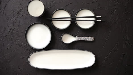 Set-of-empty-ceramic-dishes-for-sushi-and-rolls-on-a-black-stone-table