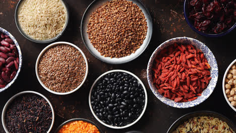 Various-superfoods-in-smal-bowls-on-dark-rusty-background