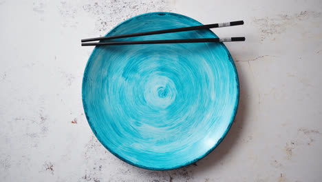 Turquoise-hand-painted-ceramic-serving-plate-with-wooden-chopsticks-on-side
