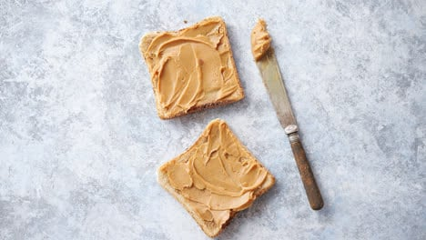 Two-tasty-peanut-butter-toasts-placed-on-stone-table