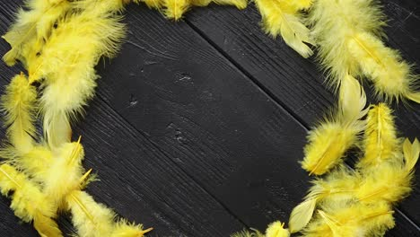 Colorful-decorative-Easter-feather-wreath-on-black-wooden-table-background