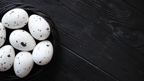 Whole-Chicken-eggs-in-a-nest-on-a-black-rustic-wooden-background-Easter-symbols