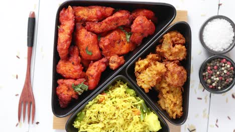 Spicy-indian-fried-chicken-served-with-curry-vegetable-rice-onion-bhajia-naan-bread
