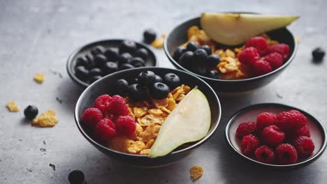 Golden-cornflakes-with-fresh-fruits-of-raspberries--blueberries-and-pear-in-ceramic-bowl