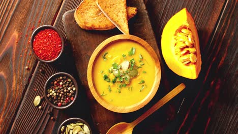 Pumpkin-soup-with-bread-on-chopping-board