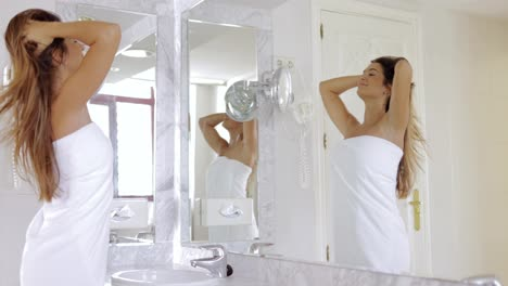 Young-woman-admiring-reflection-in-mirror