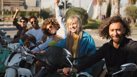 Trendy-young-friends-on-scooters-waving-at-camera