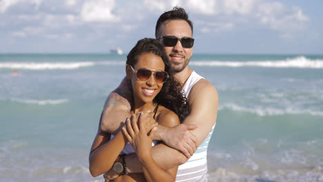 Embracing-diverse-couple-on-shoreline