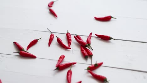 Freely-falling-small-red-chilli-peppers-on-the-white-wooden-table-Slow-motion-video