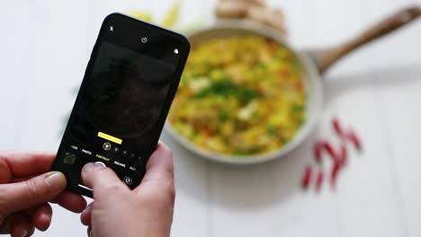 Woman-taking-a-photos-with-mobile-phone-of-delicious-fried-rice-with-chicken-served-in-pan