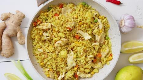 Delicious-fried-rice-with-chicken-and-vegetables-served-in-pan-Placed-on-white-wooden-table