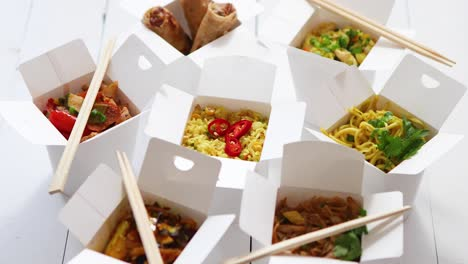Various-oriental-dishes-packed-in-paper-box-Food-is-delivered-on-the-table-Asian-take-away-concept