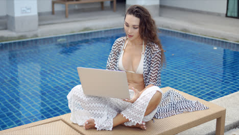Woman-using-laptop-on-poolside