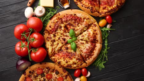 Freshly-served-three-various-pizzas-placed-among-tasty-ingredients-Top-view