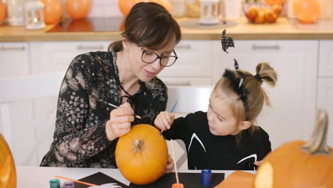 Woman-and-girl-painting-pumpkin