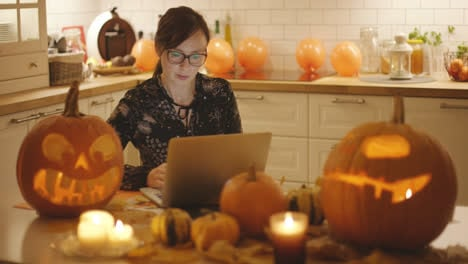 Woman-using-laptop-near-Halloween-decorations
