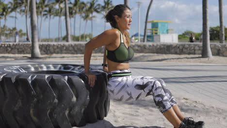 Woman-leaning-on-tire-and-exercising