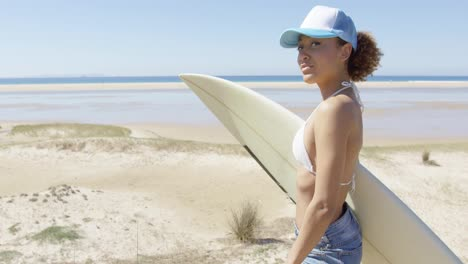Smiling-sporty-woman-embracing-surfboard