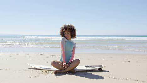 Happy-female-sitting-on-a-surfboard