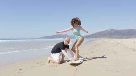 Man-teaching-woman-standing-on-surf